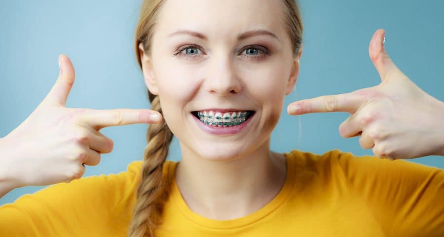 bigstock Young Woman Showing Teeth Brac 191446135